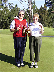 Gai Leeson and Glenda Chad with the bottles of Scotch they won for their accurate play.