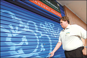 Graham Inman, the proprietor of Computer Troubleshooters in Murdock Street, with the graffiti on his newly painted roller door.