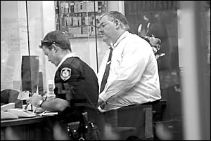 Nasty business . . . police interview Bank of Queensland branch manager Rob Anderson after Wednesday night?s hold-up. Photo: BR