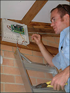 ZSS technician David Carlisle installs one of two security systems in the Yamba Buccaneers clubhouse.