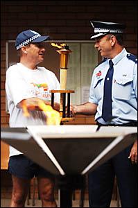 HELPING HAND: Runner, Inspector Gary Ballard, shakes hands with local Chief Inspector Darren Spooner after lighting the flame.