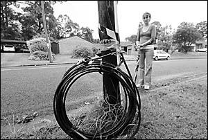 Karen Ireland examines the rolled up phone cable that was brought down by an unknown vehicle on Friday evening, cutting off ph