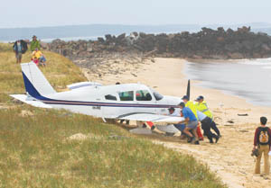Police and volunteers push the grounded Piper Cherokee away from the rising tide yesterday.