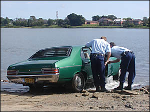 A car is pulled from the Clarence River yesterday as police inspect the cabin.