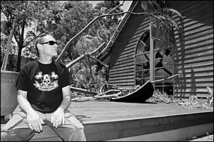 Jock Shaw stares in amazement at the damage the Mexican tree fern caused yesterday morning when it crashed onto his deck and ho