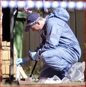 A scientific officer checks the grounds outside a Toowoomba unit in which three bodies were found. Pic: Neville Madsen