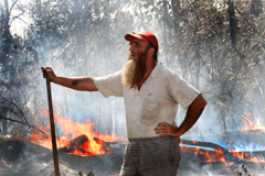 An exhausted Bradley Nelson overlooks his burnt-out property on Coonarr Road yesterday.