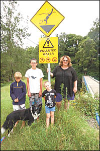 Coramba residents Corey and Brian Adam, Misty the dog, Jack Radford and Cathy Hawkins with the new ?polluted water? sign erecte