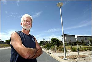 BOB Dagworthy with one of the dodgy and dangerous aluminium light poles at Casuarina Beach.  Photo: CRAIG SADLER.