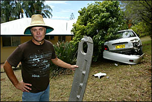 TIRED of writing letters: Mike Connelly with the rear bumper of a car that landed in his backyard.