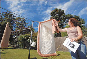 Gillian Hobson pulls her washing off the line ahead of the nightly exodus of flying foxes. She says the proposed measures are e