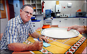 Barry Moon of Coffs Harbour St Vincent de Paul fills out food vouchers for hungry families, but the money is running out.