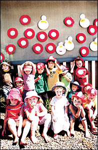 Pre-schoolers from Richmond Hill in front of a wall with plates they made to signify children with pre-school places (in white)