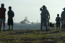 A crowd waits to meet the ship which will take the name HMAS Bundaberg as it arrives at the port yesterday.