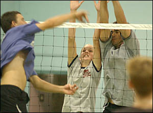 Louise Hanna, centre, double blocking with Chris Austin, right, against Chris Geary in the local volleyball competition held ev
