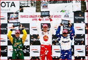 Will Power (left) celebrates his third place finish at Long Beach alongside Sebastien Bourdais (centre) and Oriol Servia.
