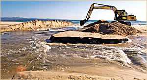 DIGGIN? IT: Byron Shire Council excavator driver Ian Cradell digs a channel to empty the lagoon at Clarks Beach yesterday. The