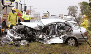 QFRS Anzac Avenue firefighter Chris Lederhose and tow truck driver Terry Bellet look over the wreckage of the vehicle.