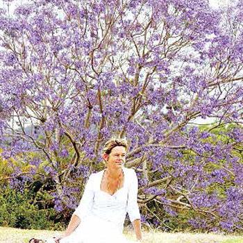 Carol Gollschewsky sits in her garden in front of a jacaranda in full bloom.