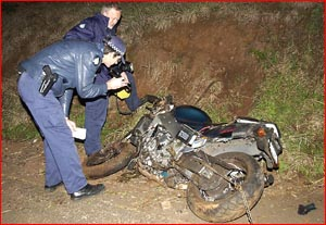 Police investigators photograph the crashed motorcycle after Saturday morning's fatal accident.