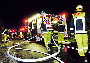 MOPPING UP: Lismore Fire Department crews in action after extinguishing a house fire on Donnans Road, Lismore Heights, last nig