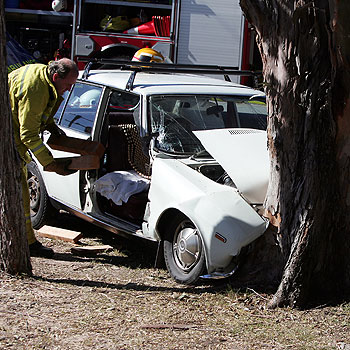 A traffic accident victim is comforted  after a vehicle crashed head on into a gum tree on the corner of Ulm and Queen Streets Caloundra.  Photo:Barry Leddicoat