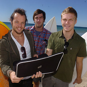 Mates Dylan Street, Nathan Dreghorn, and Ricky Geltch enjoy business meetings in the surf for their web design business Wayy.