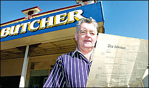 Egans Premier Meats owner John Egan holds out his butchers apprentice papers in front of the South Lismore shop where he has