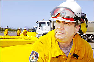 TOUGH SLOG: Volunteer rural firefighter Ian Leckie, of Tuncester, takes a brief break from filling the planes used to water bom