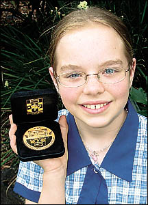 Alice Matheson, 11, with the gold medal she received for scoring full marks in a NSW/ACT English exam.