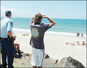 Surfer Ian Penfold and police scan the site on Byrons Main Beach where a mako shark was seen minutes earlier.