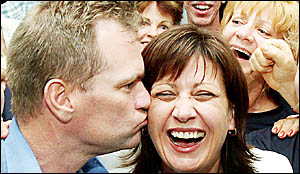 Craig Elliot gives his wife Justine a celebration kiss after she won her Richmond seat by an increased margin.