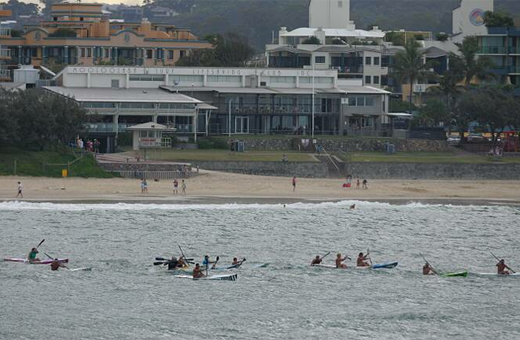 Ski paddlers train in the bay at Mooloolaba, Mooloolaba Surf Club and lifeguard tower in background. Photo: Brett Wortman/bw170689r