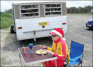 Lifeguard Amanda Berry enjoys Christmas lunch on the job in front of the vandalised caravan.