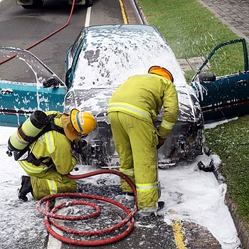 Firefighters inspect the damage to a car that caught fire with an elderly couple inside on the David Low Way at Coolum Beach. Photo: Jason Dougherty/171377d
