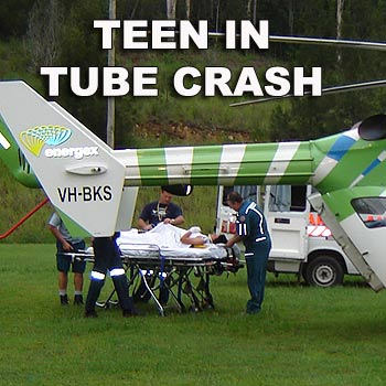 A 15-year-old boy is treated by paramedics after suffering spinal injuries in a ski tube accident at Sommerset Dam, near Kilcoy. Photo: Energex Community Rescue Helicopter