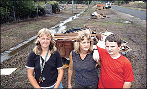FLOOD MESS: Flood victim Kerry OConnor (centre), Krystal Faint and her son Rory, 10, with flood rubbish piled up in the street