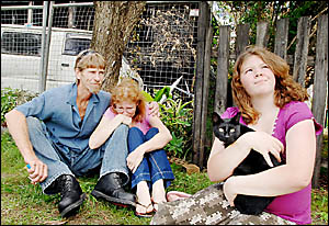 CLOSE CALL: Gavin Bright comforts Jacqueline Carey and her daughter Aleasha, pictured holding her cat Ziggy outside their burnt