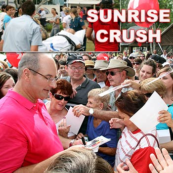The crowd crushes in to meet Sunrise's David Koch while a woman is taken away by paramedics after collapsing during the Cotton Tree broadcoast today. Photo: Jason Dougherty.