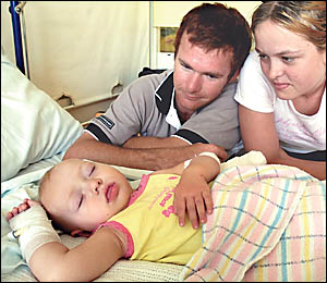 Daniel Clements and Sally Mills, from Urbenville, watch over their sleeping daughter Emi  Clements, who was bitten by a black s