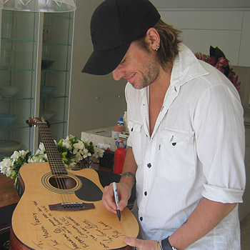 Country music star Keith Urban signs the guitar for the Coolum Surf Life Saving Club fundraiser.