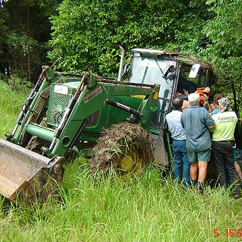 Paramedics work to help free a man, 67, trapped, after his tractor rolled down an embankment at Peachester late Tuesday. Photo: Energex Community Rescue Helicopter.