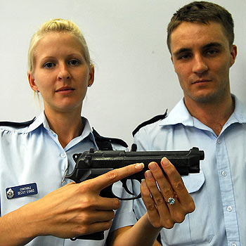 Constable Beckie Evans (left) and Constable Andrew Mckie showing the replica gun which almost cost a coast man his life yesterday. The man produced the gun in front of the officers, who were unsure if the gun was real or not. Photo: Che Chapman