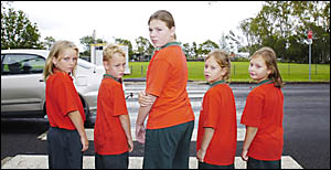 SCHOOL CROSS (ING): Concerned at the risk posed by passing cars and trucks, Kyrie Zwiebe, 9, Jacob Hyde, 7, Sarah Sivewright, 1