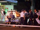 A man shot by two men in a blue Mitsubishi Lancer in a drive-by shooting out Nambour's Royal George Hotel is taken into an awaiting ambulance. Photo: Jason Dougherty.