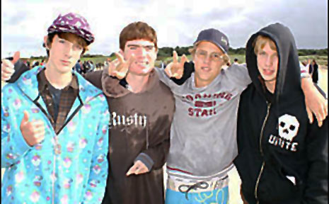From left, Brock Curtis-Mathew, Sam Patterson, Daniel Hotschilt and Jamie Hannah embrace in unity after placing white roses in the surf.