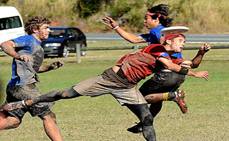 Players from Sublime, WA (in the blue) and Chilly, Vic (in the red) battle it out in the mud.
