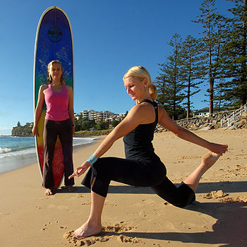 Belinda Wehner, from Broulee Surf School, and Tammy Pascoe, from  Yoga Energy, balance mind and body on Moffat Beach. Photo: Warren Lynam/174400d