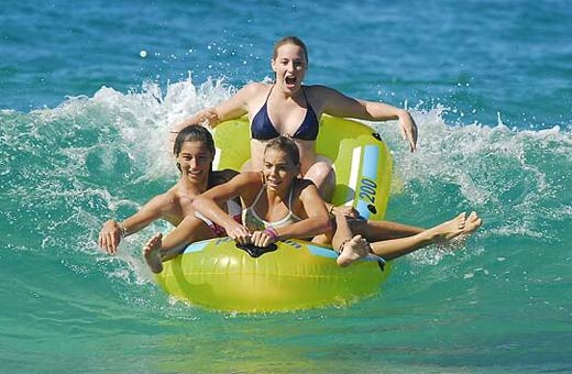 Mountain Creek State High students, Jordy Jones, Rhiannon Paul and Katie Nawrath, took to the waves in an inflatable boat at Kawana. Photo: Che Chapman / 174546b