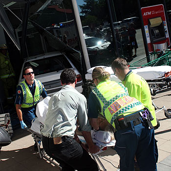 Emergency workers help one of the victims of the crash at the Credit Union Australia branch in Nambour. Photo: Jason Dougherty/ 174589d